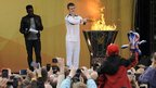 Phil Fuller, the last torchbearer of the day, lights the cauldron in Leicester's Abbey Park