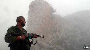 "A member of the Free Syrian Army stands near the ""Al-Hosn"" Crusaders Citadel on the outskirts of flashpoint city of Homs"