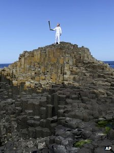 "Peter Jack holds the Olympic torch aloft at the Giant""s Causeway"