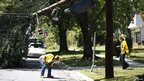 Power company employees inspect damaged overhead power lines to assess emergency repairs in Wheaton, Maryland, 2 July 2012