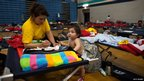 One-year-old Danny Melendez and his mother rest in a Red Cross shelter set up at Northwestern High School in Hyattsville, Maryland, 30 June 2012