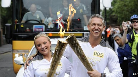 Gary Lineker passes the Olympic flame on to Pennelope Allman