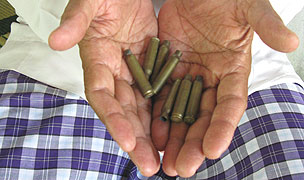 A principal in Pattani, Thailand holds spent bullet casings.