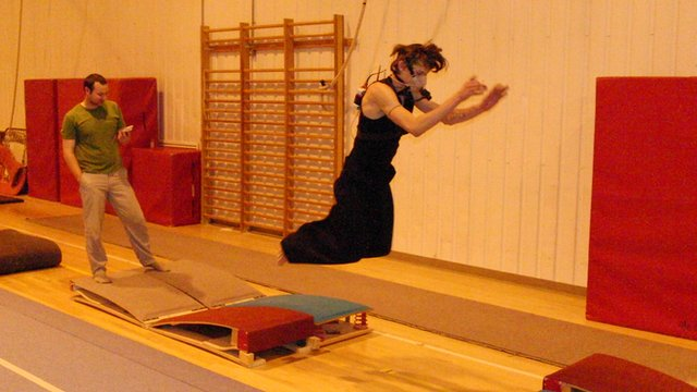 Parkour athlete wearing oxygen-measuring equipment performing in a gym