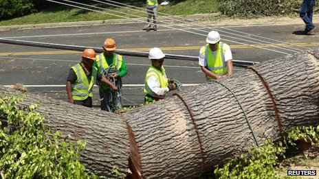 Utility workers try to free up power lines after a huge tree fell across major road in Falls Church, Virginia 2 July 2012