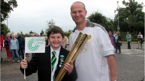 School Reporter holds an Olympic torch