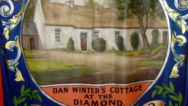 This banner depicts the cottage of Dan Winter, one of the founders of the Orange Order, and is reputed to be where the decision was taken to found a brotherhood for all Protestants, named for William of Orange
