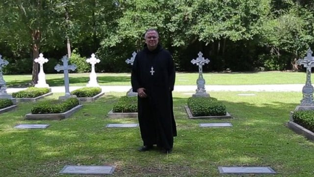 A monk stands in a graveyard