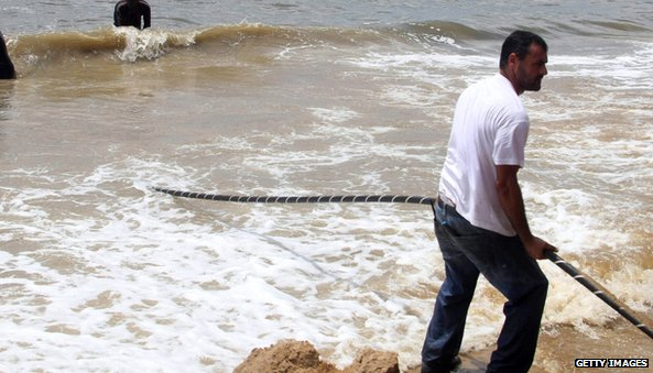A man pulls an internet cable over the African shoreline