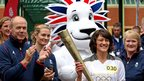 Torchbearer Audrey Cooper holds the Olympic flame at Loughborough University with the British Olympic Association's Director of Elite Performance Sir Clive Woodward to her left and the Team GB mascot Pride the Lion behind her, 3 July 2012.