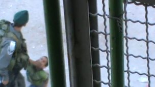 Screengrab of video showing Israeli Border Police officer holding down Abdul Rahman Burqan