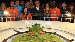 "Danny Boyle (centre) with Olympic volunteers and a model of the ""British countryside"" set"
