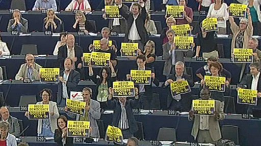 MEPs holding up anti-Acta signs during the voting session in the European Parliament