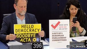 "Member of European Parliament holds sign reading ""Hello democracy, goodbye Acta"""