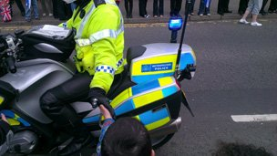 Harrison Barnes, five, gets a high-five from a passing police motorcyclist in Alloa, pic courtesy of Chris Barnes