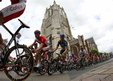 The pack of riders cycles past the church of Aire-sur-la-Lys