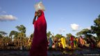 A refugee carries water in South Sudan