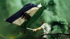 A football fan was a flag amidst green smoke from a flare
