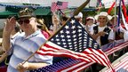 A Korean War veteran waves as he participates in a July 4th parade in The Woodlands, Texas 4 July 2012