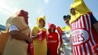 Spectators dressed as ketchup, mustard and other relishes wait for Nathan's Famous Fourth of July International Eating Competition at Coney Island, New York 4 July 2012