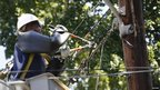 An electrician works on restoring power in Wheaton, Maryland 4 July 2012