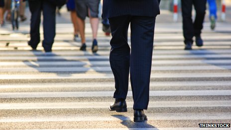 Business people walking across pedestrian crossing
