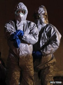 Officials in protective gear stand next to people from the evacuation area near the Fukushima Daini nuclear plant, in Koriyama, 13 March 2011