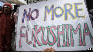 "A demonstrator holds a ""No more Fukushima"" sign during a rally against restarting the Ohi nuclear power plant reactors in front of the prime minister's official residence in Tokyo, on 16 June 2012"