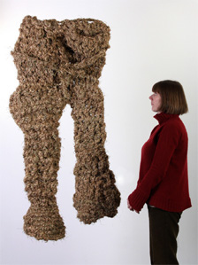 Woman looking at trousers woven from grass by Angus MacPhee