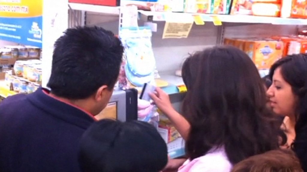 People using a prepaid card in a supermarket.