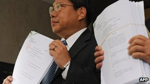 Albert Ho displaying court papers to the press on 5 July 2012