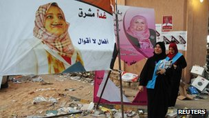 Majdah al-Fallah (L) and Hannan Bachir, candidates for the Justice and Construction Party walk past defaced campaign posters in Tripoli