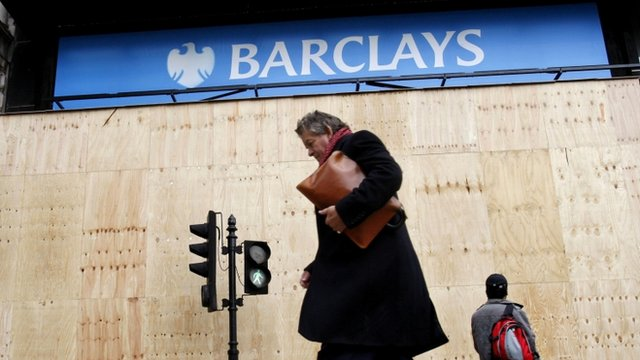 Pedestrians walking past a Barclays bank logo in central London