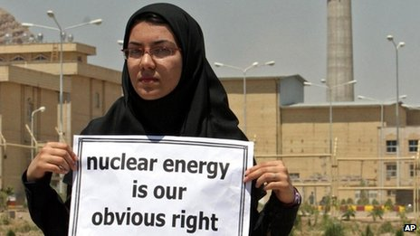 An Iranian student holds up a sign in support of nuclear energy at an enrichment facility in Esfahan