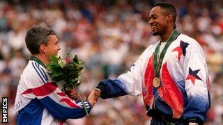 Jonathan Edwards and Kenny Harrison shake hands on the podium