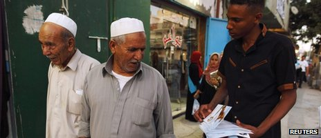 A member of the Justice and Construction Party, the political arm of the Libyan Muslim Brotherhood, hands out brochures of his party candidates to people during their election campaign in a suburb of Tripoli, 4 July 2012