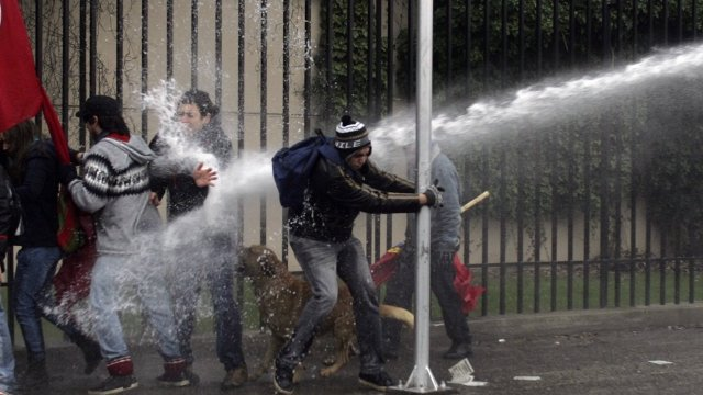 Demonstrators are hit by a jet of water as they clash with riot policemen in Chile