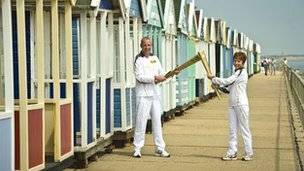 Richard Game passes the flame to Torchbearer Caroline Emeny in front of the Southwold beach huts