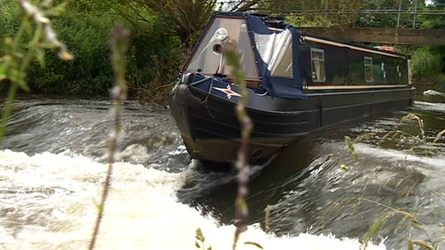 Narrowboat stuck on a weir in the River Soar