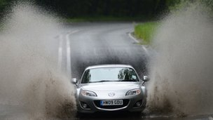 Car driving through a large puddle