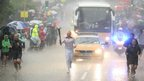 Glenn Chambers carrying the Olympic flame in heavy rain during his stint between Edwinstowe and Mansfield, day 41