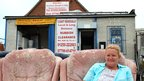 Debbie Gleeson sitting outside her used furniture shop, Deb's Den in Jaywick, Essex