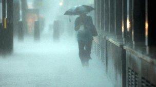 Woman walks with umbrella in heavy rain