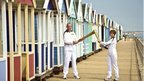 Richard Game passed the Olympic flame to Caroline Emeny in front of the beach huts at Southwold.