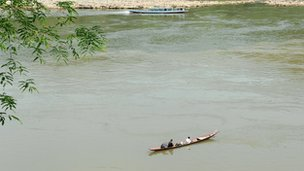 Laotian men fish from their boat in the Mekong river in Luang Prabang