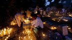 Kashmir Shia Muslims offer prayers at candle-lit graves
