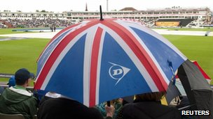 Spectators shelter from the rain at Edgbaston, 4 July