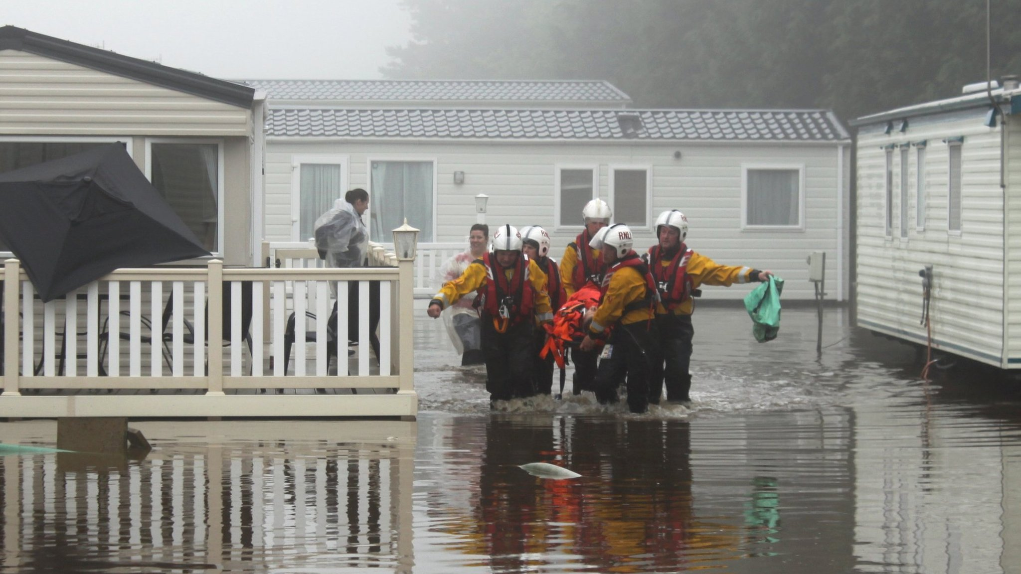Lifeboat crew rescuing people from static caravan