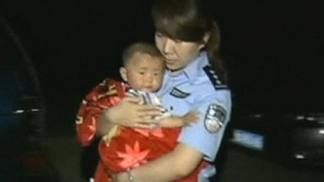 Police officer holding child