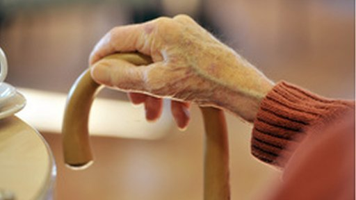 Elderly hand clutching a walking stick